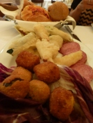Fried olives, fried zucchini flowers and salami