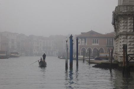 A lone gondola navigates the fog on the Grand Canal