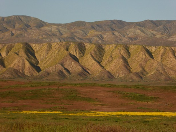 The San Andreas Fault running along the base of these hills